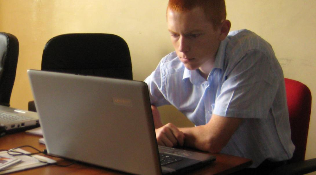 A Projects Abroad volunteer doing an IT teaching internship in Ghana checks the functionality of the computers in a school.